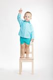 Boy on chair and pointing his finger up. Little boy standing on chair and pointing his finger up Royalty Free Stock Photos