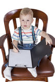 Boy in the chair writes Stock Images