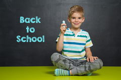 Boy with chalk and school board with text BACK TO SCHOOL Stock Images