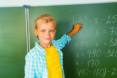 Boy with chalk stands near blackboard and looking Stock Photography
