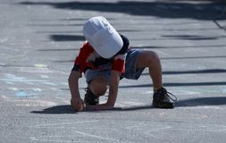 Boy chalking a message stock photography