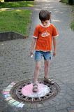 Boy chalking the street
