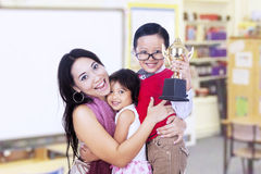 Boy champion and family in classroom Stock Image