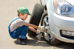 Boy changes the wheel. Little boy repairing a car Royalty Free Stock Photography