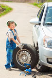 Boy changes the wheel Royalty Free Stock Image