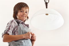 Boy changing a lightbulb in ceiling lamp. Holding incandescent and fluorescent bulbs standing under the lamp-shell stock image