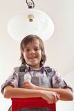 Boy changing lightbulb in ceiling lamp. Smiling on the top of ladder holding a fluorescent bulb royalty free stock photos