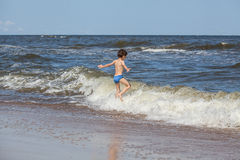 Boy chasing a waves Stock Photos