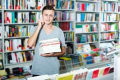 Boy chatting on mobile phone and searching book. Positive teenage boy chatting on mobile phone and searching book in shop Royalty Free Stock Images