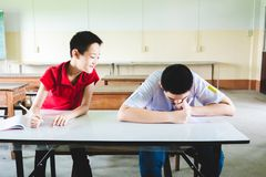 Boy cheating in the test by copying from the another boy royalty free stock image