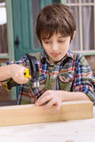 Boy in checkered shirt hammering nail in wooden plank Royalty Free Stock Photo