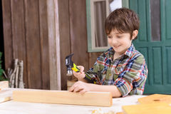 Boy in checkered shirt hammering nail in wooden plank Stock Photos