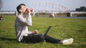 Boy checking laptop and receives good news. A man is sitting in the park Man just have won a huge prize,finally it happened. A student, a freelancer, smiles stock footage