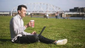 Boy checking laptop and receives good news. A man is sitting in the park Man just have won a huge prize,finally it happened. A student, a freelancer, smiles stock video footage