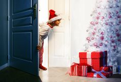 Boy checking presents under Christmas tree. Little curious handsome boy checks presents under Christmas tree looking from the door  in the night Royalty Free Stock Photo