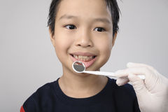 Boy checking tooth by mirror Royalty Free Stock Image
