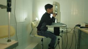 Boy checks eye vision in ophthalmology clinic - wide angle. Slider shot stock footage