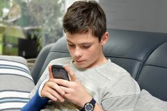 Boy checks the messages on his  cellphone. Arm in blue cast. teenage boy with broken wrist plays with his cellphone and checks messages Royalty Free Stock Photo