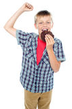 Boy cheering and enjoying choco chip cookie. All against white background Royalty Free Stock Photography
