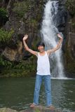 Boy cheering at waterfall. Asian teenage boy cheering and shouting with arms up enthusiastically in front of a tropical waterfall and enjoying the tropical Royalty Free Stock Photo