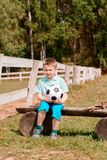 A boy cheerleader sits with a football on the field on the bench watching football. royalty free stock photos