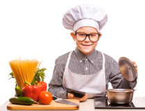 Boy chef is cooking in the kitchen Stock Images
