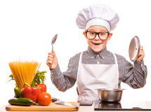 Boy chef is cooking in the kitchen Stock Image