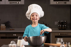 Boy in chef hat cooking in the kitchen. Stock Photo