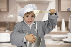 Boy with chef hat and outfit making paste Stock Image