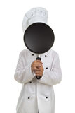 Boy chef hiding his face behind the black frying pan Stock Photography