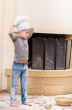 A boy in chef`s hats near the fireplace sitting on the kitchen floor soiled with flour, playing with food, making mess Royalty Free Stock Photography