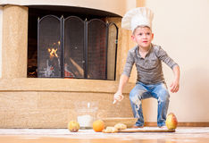 A boy in chef`s hats near the fireplace sitting on the kitchen floor soiled with flour, playing with food, making mess Stock Images