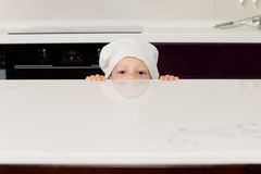 Boy in a chefs hat peering over the counter Royalty Free Stock Photo