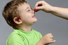 Boy and cherry Royalty Free Stock Images