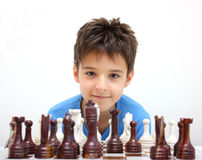 A boy and chess. A boy looking camera during chess game isolated on a white background Stock Photo