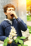 Boy with chestnut flowers sneezing from allergy Stock Photography