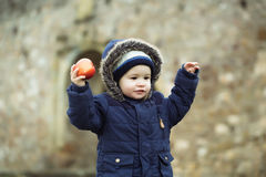 Boy child with apple in autumn jacket Stock Photo