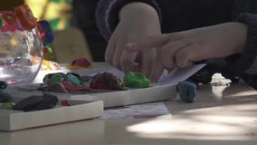 Boy child arms sculpts figures out of plasticine on table at home. Boy child arms sculpts figures out of plasticine on table stock video