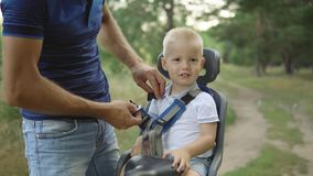 Boy in child bike seat, father wear a seat belt Stock Images