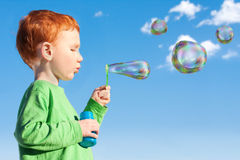 Boy child blowing soap bubbles into sky. Boy child blowing soap bubbles outside with blue sky Royalty Free Stock Image