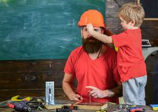 Boy, child busy play with protective helmet, learning to use tools with dad. Father, parent with beard teaching little. Son to use different tools in school stock photos