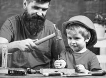 Boy, child busy in protective helmet learning to use hammer with dad. Father with beard teaching little son to use tools. Hammering, chalkboard on background royalty free stock photo