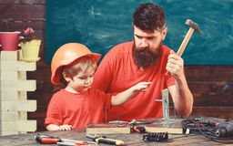 Boy, child busy in protective helmet learning to use hammer with dad. Father with beard teaching little son to use tools. Hammering, chalkboard on background stock image