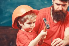 Boy, child busy in protective helmet learning to use hammer with dad. Fatherhood concept. Father with beard teaching royalty free stock photo