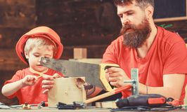 Boy, child busy in protective helmet learning to use handsaw with dad. Masculine duties concept. Father, parent with royalty free stock photo