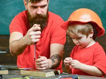 Boy, child busy in protective helmet learning to use screwdriver with dad. Father, parent with beard teaching little son. To use tool screwdriver. Handyman and Royalty Free Stock Photography
