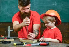 Boy, child busy in protective helmet learning to use screwdriver with dad. Repair and workshop concept. Father, parent. With beard teaching little son to use Stock Photo