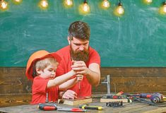 Boy, child busy in protective helmet learning to use screwdriver with dad. Teamwork in workshop concept. Father, parent stock photos