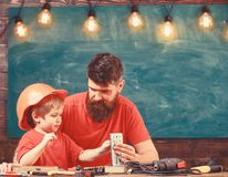 Boy, child busy in protective helmet makes by hand, repairing with dad. Father with beard teaching little son to use. Tools in classroom, chalkboard on stock images