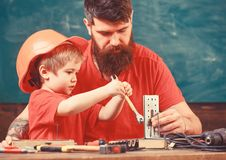 Boy, child busy in protective helmet makes by hand, repairing, does crafts with dad. Father with beard teaching little royalty free stock image